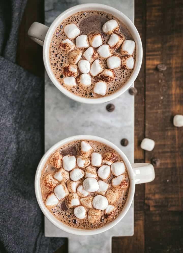 Two white mugs of hot chocolate topped with marshmallows on a marble cutting board.