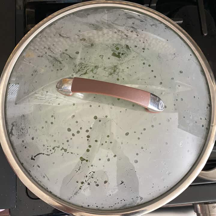 A covered skillet cooking the green beans.