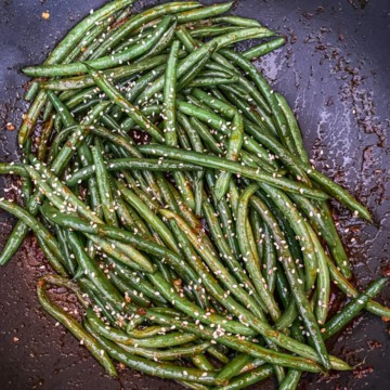 A skillet with asian-style green beans topped with sesame seeds.
