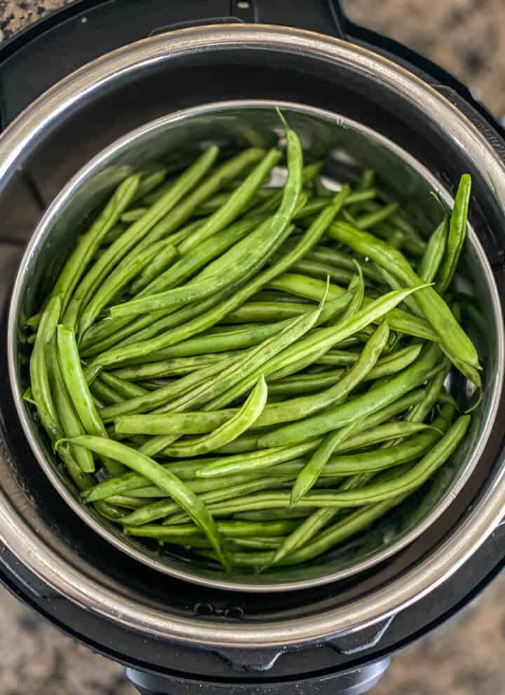 An instant pot with green beans in a steamer basket.