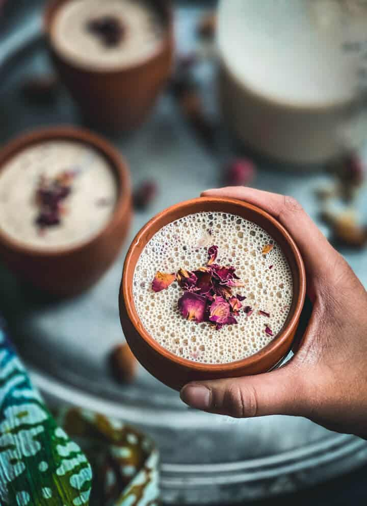 A hand holding a brown mug with thandai and topped with rose petals in front of a tray of thandai.