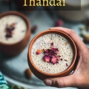 A hand holding a brown mug with thandai topped with rose petals in front of a silver plate with other mugs of thandai topped with rose petals and the word Thandai in yellow in the top middle of the picture.