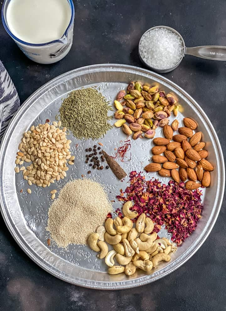A silver platter with nuts, seeds, and spices used to make thandai.
