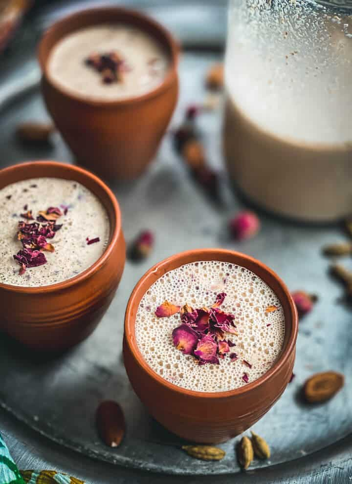 A silver platter with brown mugs of thandai topped with rose petals and a glass mug of thandai in the back right.