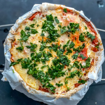 A parchment paper lined springform pan with a fully cooked instant pot lasagna topped with chopped parsley.