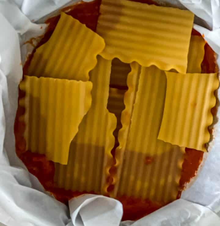 A springform pan lined with parchment paper with sauce and a layer of noodles.
