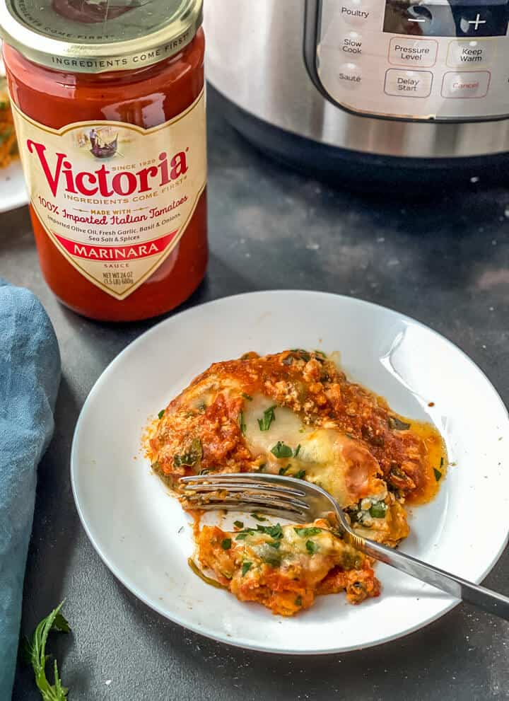 A white plate with a slice of instant pot lasagna with a silver fork and a jar of Victoria pasta sauce in the back left.
