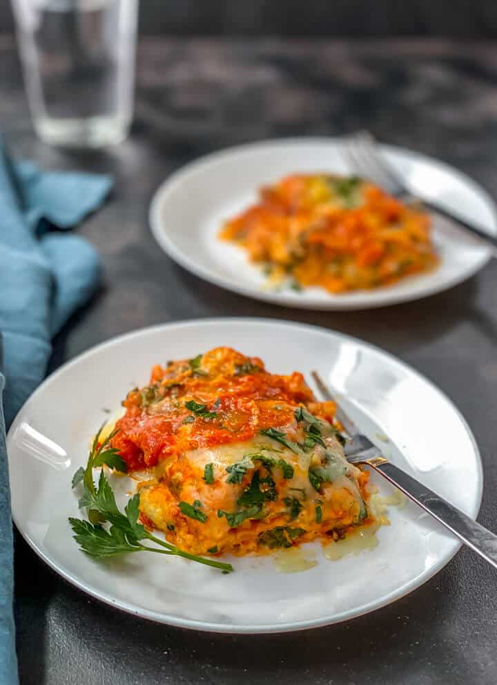 A white plate with a serving of instant pot lasagna with a silver fork and another serving of lasagna on a white plate in the back with a blue towel to the left.