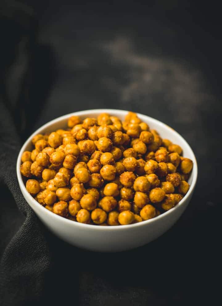 A white bowl with air fryer roasted chickpeas on a black towel.