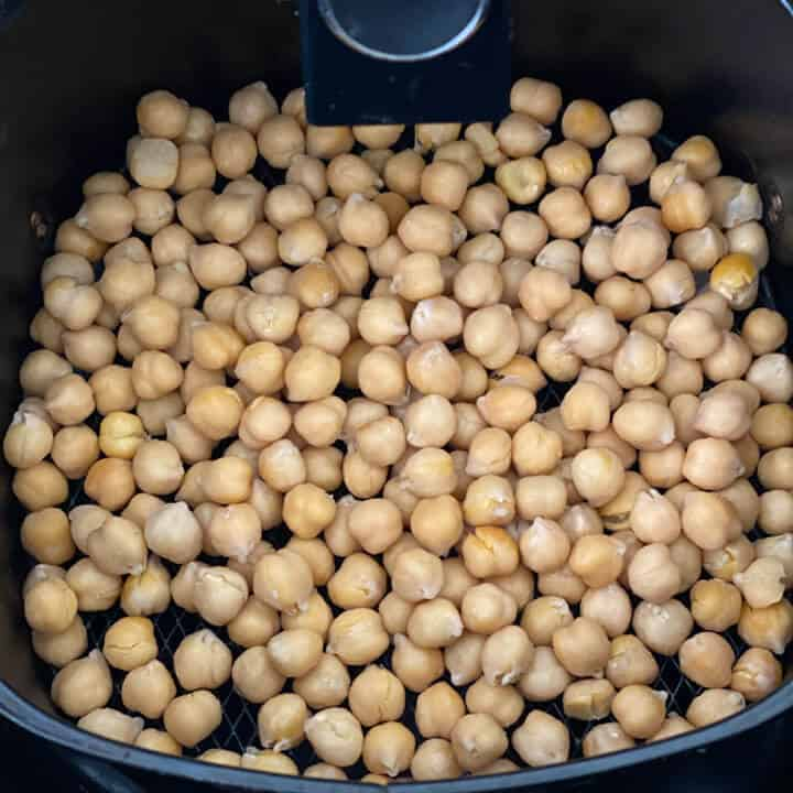 Uncooked chickpeas in the air fryer before roasting.