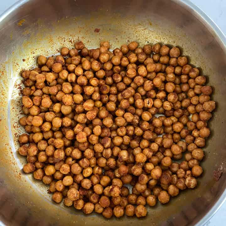 Fully seasoned chickpeas in a bowl coated with oil and spices.