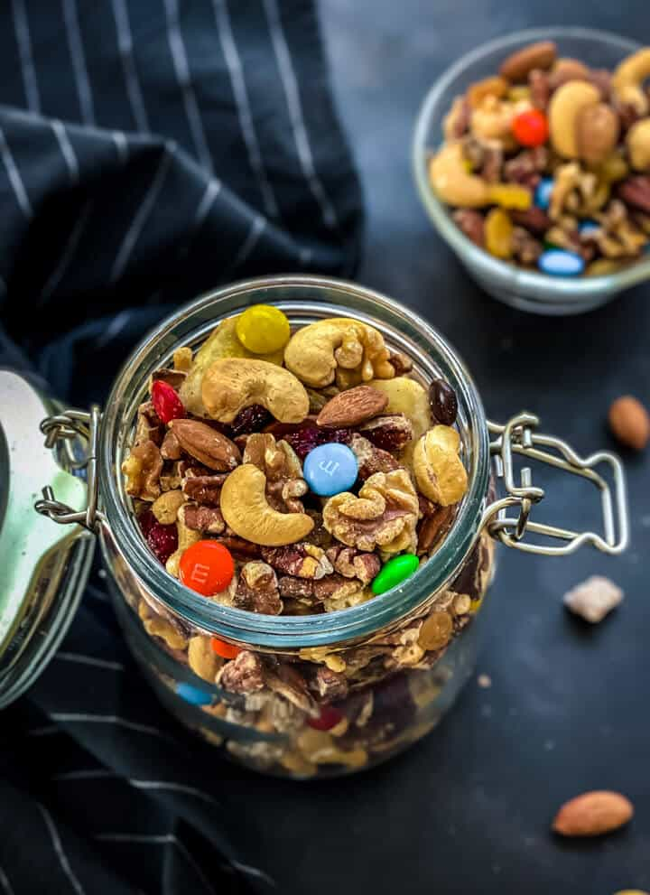A glass jar filled with easy trail mix with a small bowl of homemade trail mix in the back on a dark grey counter.