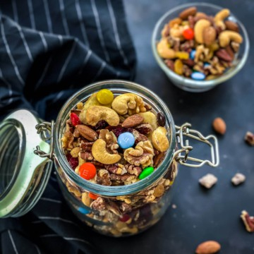 A glass jar with a lid attached on the left side with the lid hanging open and homemade trail mix inside the jar with a small glass bowl of homemade trail mix in the back.