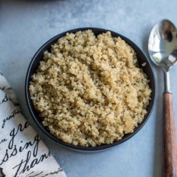 A black bowl with fluffy quinoa and a silver spoon with a wooden handle to the right.