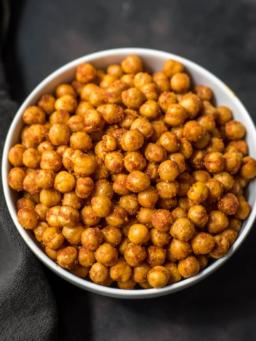 A white bowl with spicy roasted chickpeas on a black towel.
