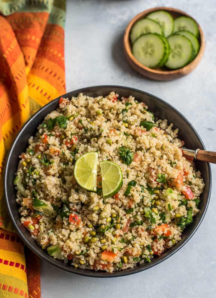 A top down photo of a black bowl filled with easy quinoa salad and topped with two slices of lime and a spoon in the top right of the bowl with a colorful dish towel to the left side and a small wooden bowl with cucumbers in the back.