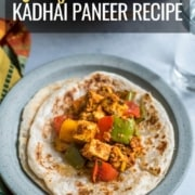 A blue plate with parathas topped with kadhai paneer a glass of water to the right and a wok with more kadai panner above with the words easy Kadhai paneer recipe at the top.