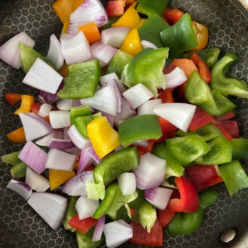 Bell pepper and onion in a wok cooking.