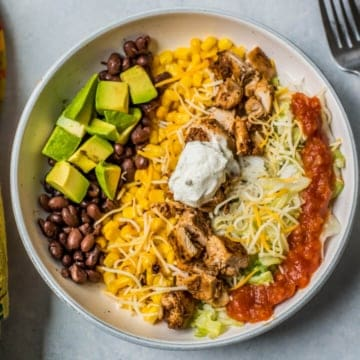 chipotle chicken burrito bowl in a white serving bowl with sour cream for lunch or dinner