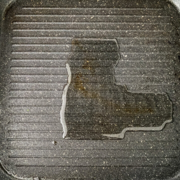 Oil heated in a black grill pan