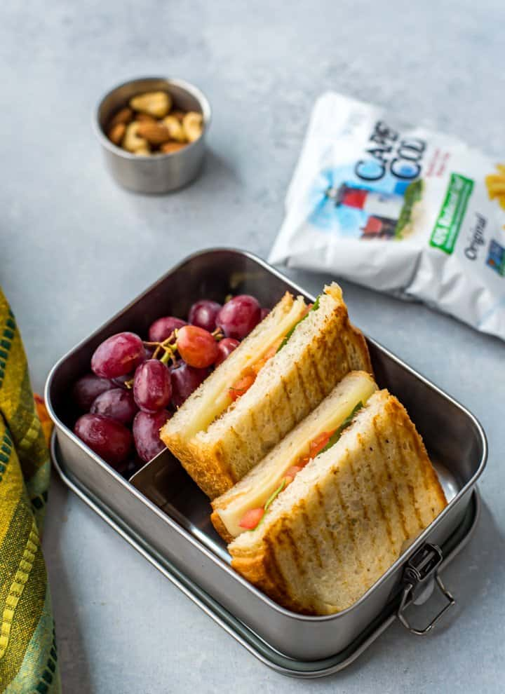 Caprese Sandwich with grapes, chips and mixed nuts on the side.