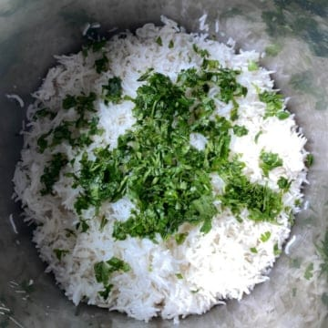 Chopped fresh cilantro added to cooked lime basmati rice inside of instant pot insert