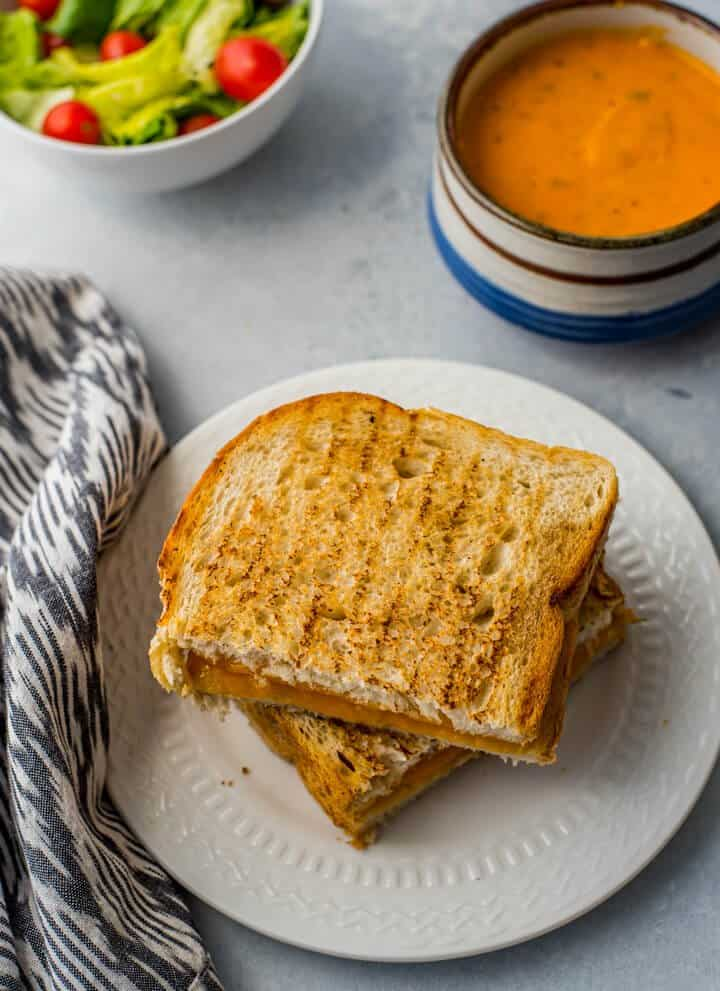 grilled cheese sandwich on white plate with tomato soup