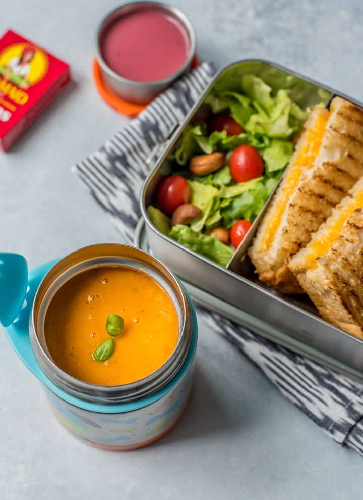 Tomato soup in a thermos with grilled cheese in a steel container along with salad and dressing. Raisins are on the side.
