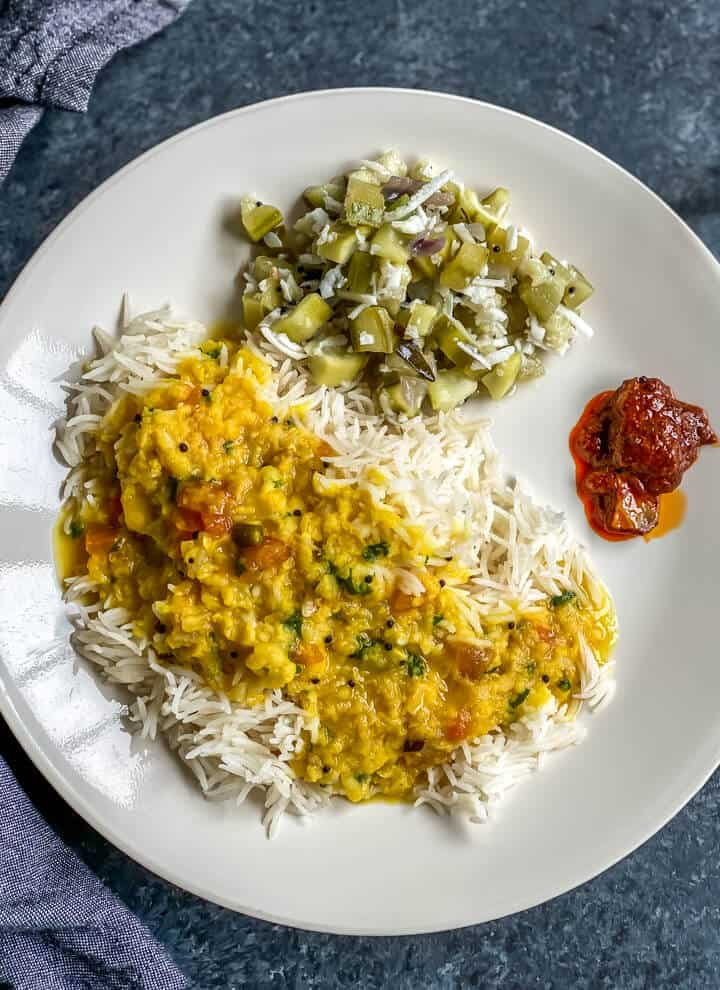 Rice, dal and turiya bhaji served with pickle on a white plate